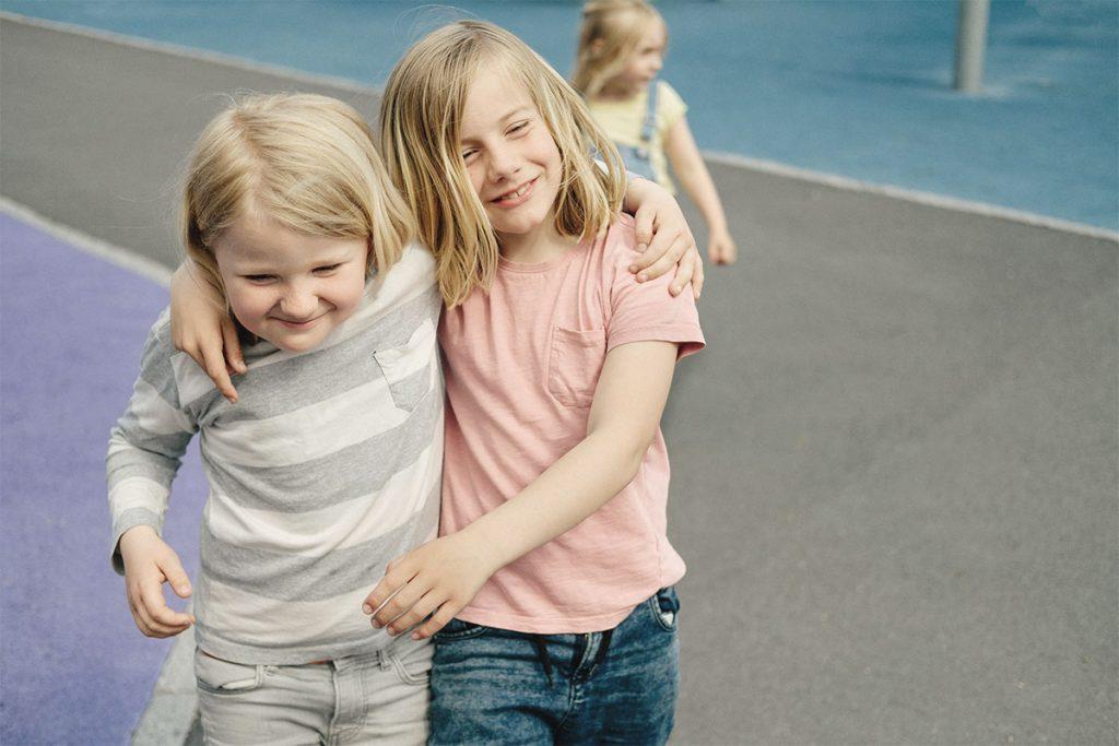 To smilende barn, skulder til skulder. Foto